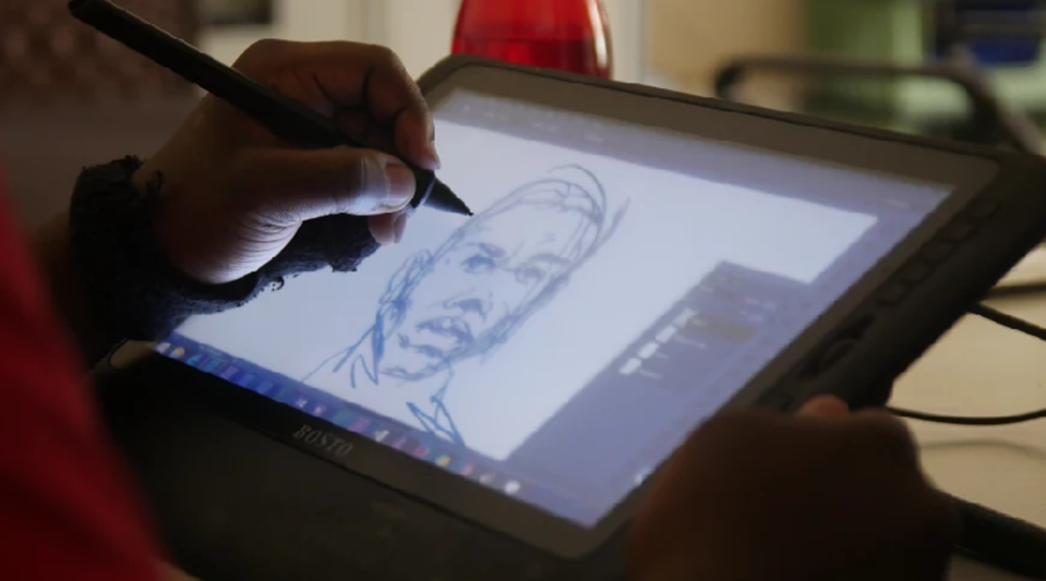 Emmanuel Nyakwada, an artist who goes by the name Point Blank Evumbi, works on a sketch using a digital drawing tablet.