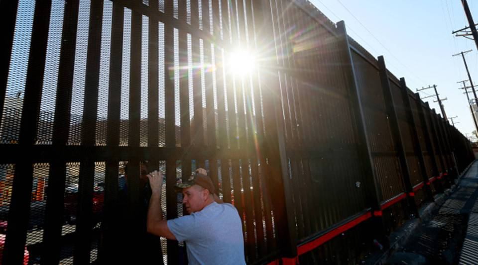 A man stands on the U.S. side of the U.S.-Mexico border wall in Calexico, California.
