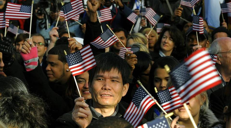 Candidates for U.S. citizenship wave flags before being sworn in during a naturalization ceremony on Liberty Island in 2011.