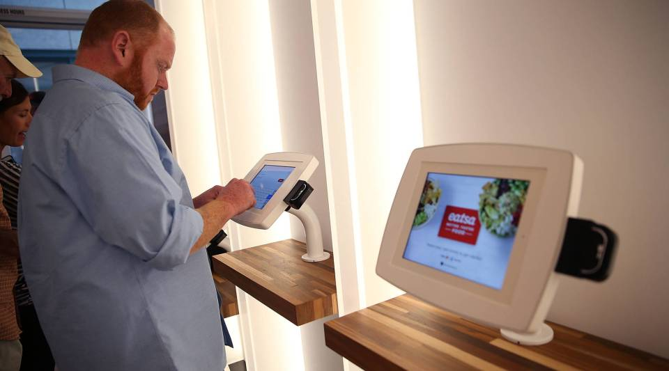 A customer uses an interactive kiosk to place an order at a San Francisco Eatsa in 2015.