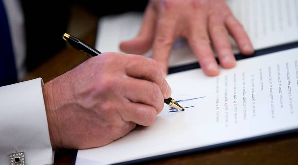 President Donald Trump signs one of five executive orders related to the oil pipeline industry in the Oval Office of the White House January 24, 2017 in Washington, DC.
