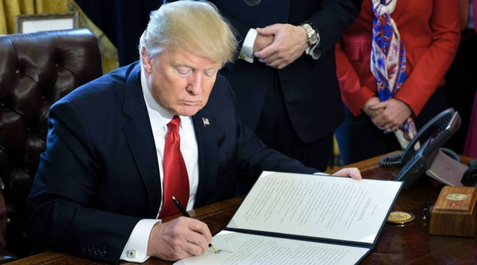 President Donald Trump signs executive orders, including one to review the Dodd-Frank financial reform law, under which the Consumer Financial Protection Bureau was created.
