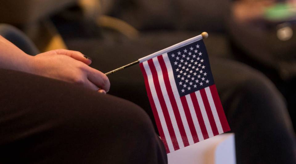 A woman holds an American flag during a naturalization oath ceremony  in Boston.