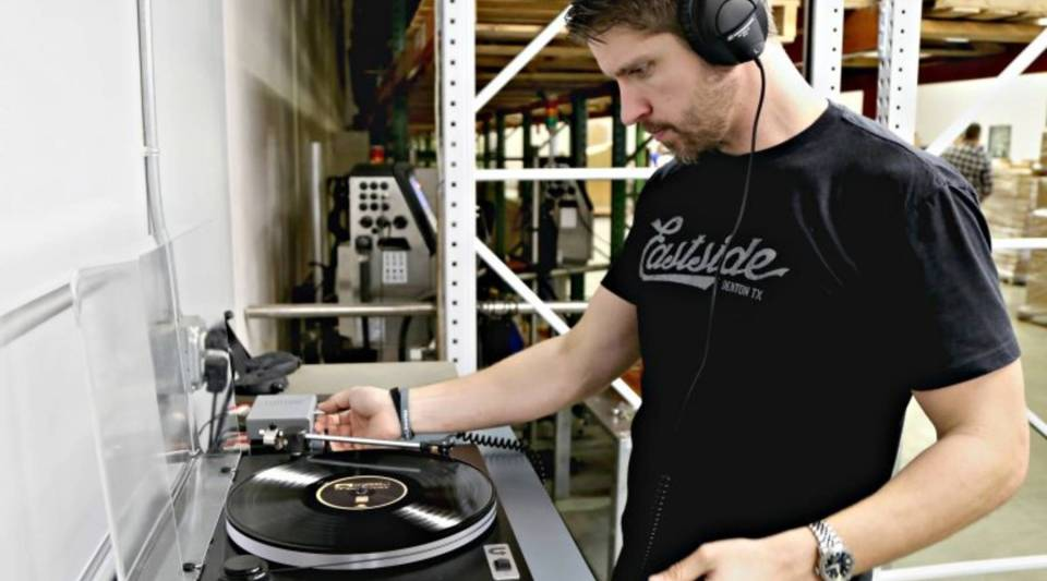 Dustin Blocker listens to records for imperfections on the floor of the manufacturing facility.