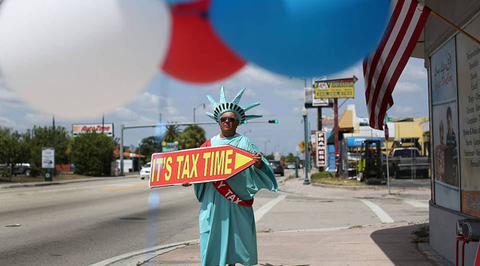 Armando La Rosa directs people to the Liberty Tax Service office as the deadline to file taxes looms on April 15, 2016 in Miami, Florida.