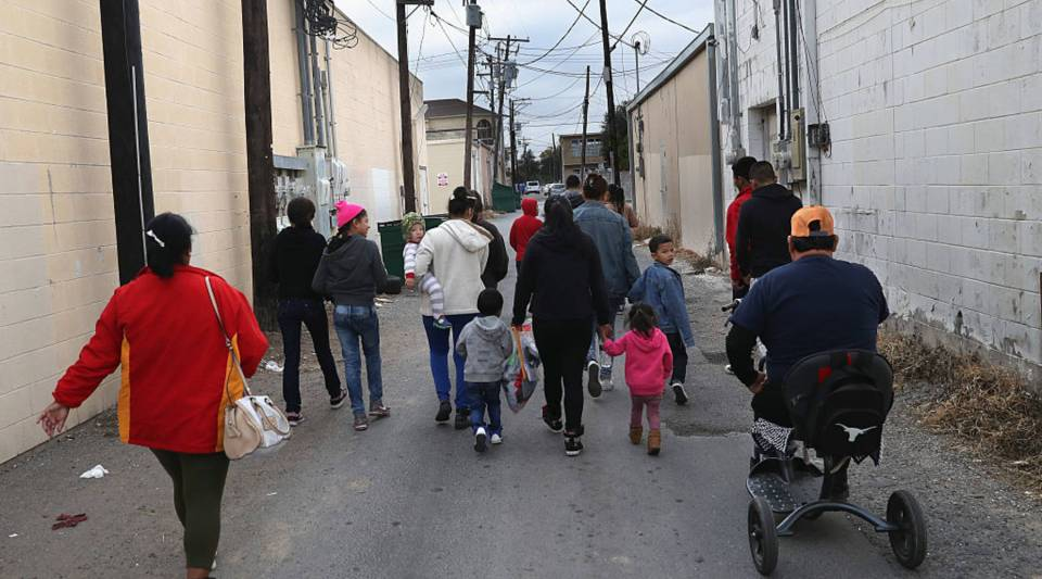 """Immigrant families in McAllen, Texas, walk to a Catholic-run """"immigrant respite center"""" before taking a bus from the border into the interior of the United States."""