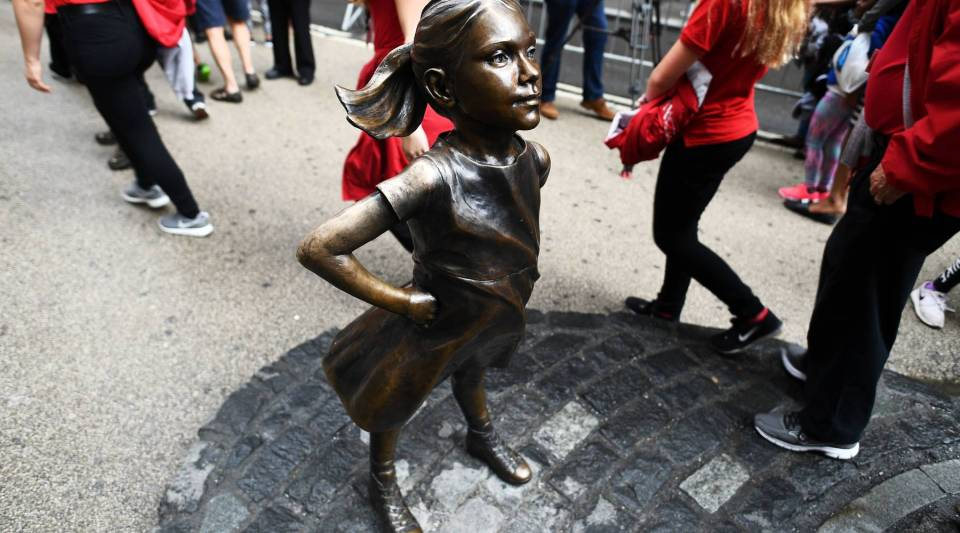 "The ""Fearless Girl"" statue stands facing the 'Charging Bull' as tourists walk by."