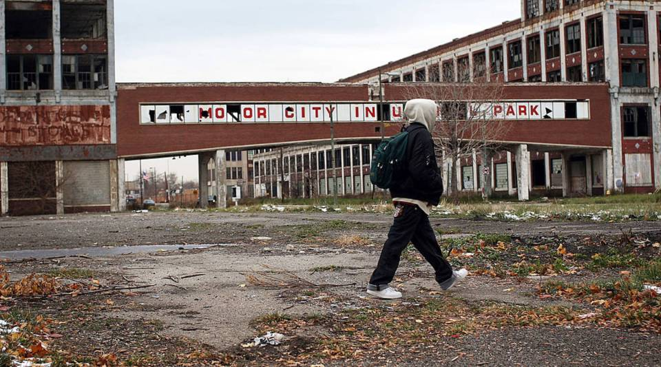 A person in Detroit walks past the remains of the Packard Motor Car Co., which ceased production in the late 1950s.