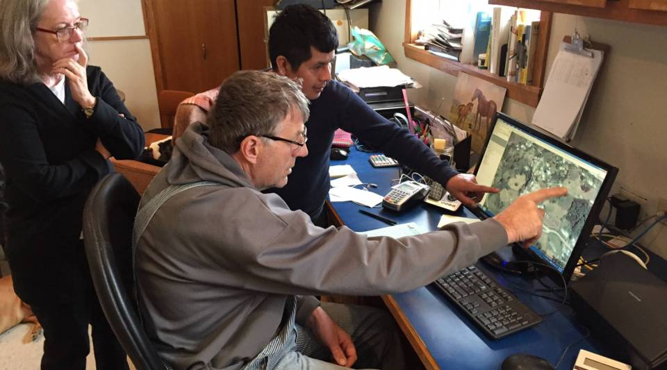 Wisconsin farmer John Rosenow looks at a Google Earth rendering of the area in Veracruz, Mexico, that many of the workers at his dairy farm call home. With him are Roberto, a worker, and Shaun Duvall, a local Spanish teacher.