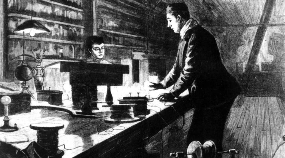 Thomas Edison works on the electric light bulb in his laboratory.
