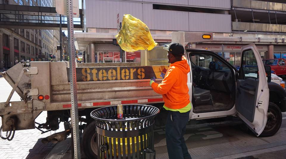 Robert Sledge, from the Department of Public Works, empties trash cans in downtown Pittsburgh.