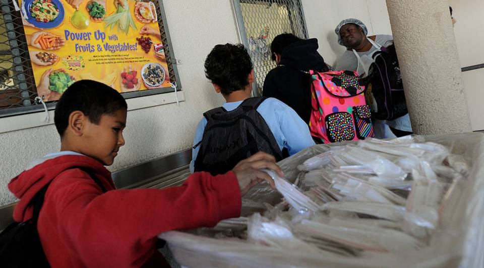 School children pick up their lunches from the cafeteria at the Normandie Avenue Elementary School in Los Angeles.