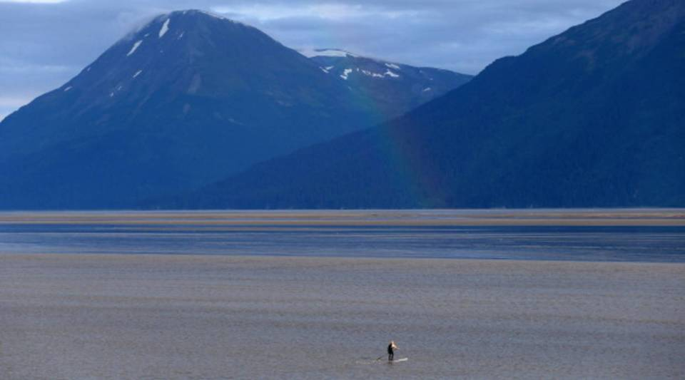 A light rainbow hits the water as a surfer waits to catch the Bore Tide at Turnagain Arm in Anchorage, Alaska.