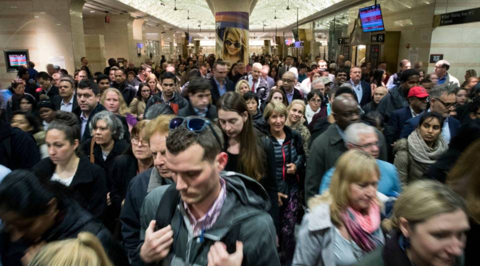 Evening commuters make their way toward a New Jersey Transit train platform at Penn Station in New York City.