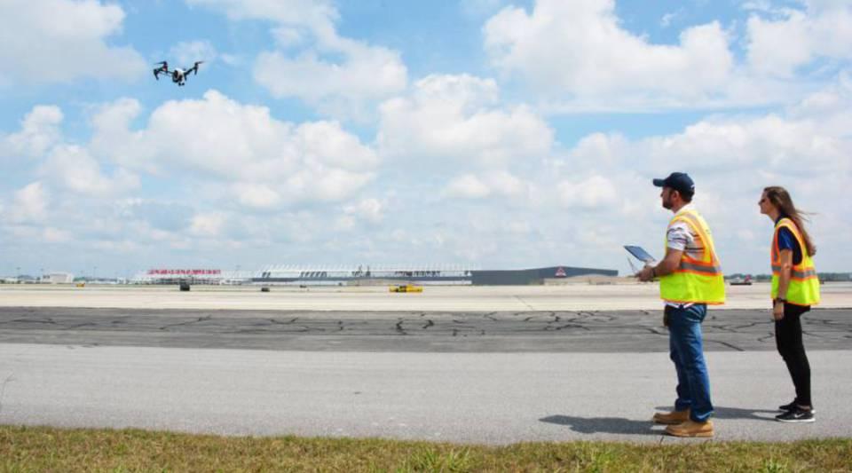 Jim Duguay and Katie Eleam pilot a drone over runway 27R at Hartsfield-Jackson Atlanta International Airport.