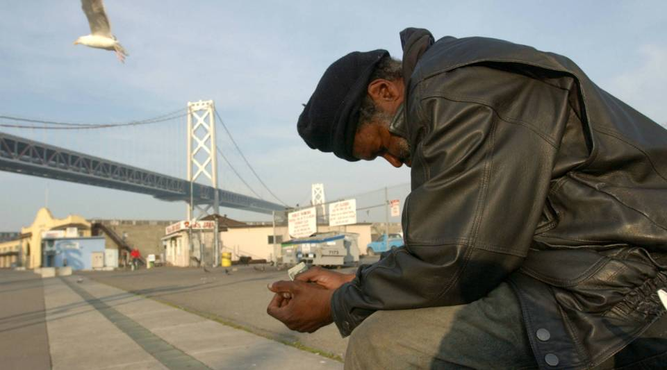 Maceo Grigsby, a homeless man, sits by a waterfront in San Francisco, California.