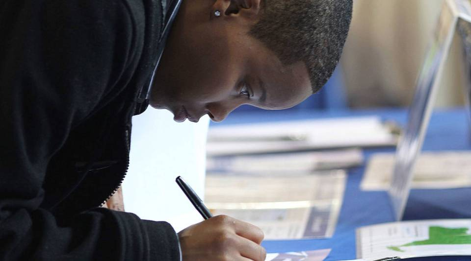 A teenager fills out an application at a job fair in the Queens borough of New York City.
