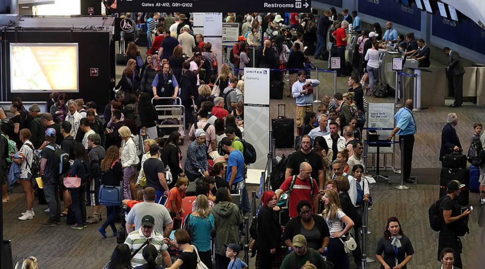 Travelers wait in long lines to speak with airline ticket agents in the United terminal at San Francisco International Airport.