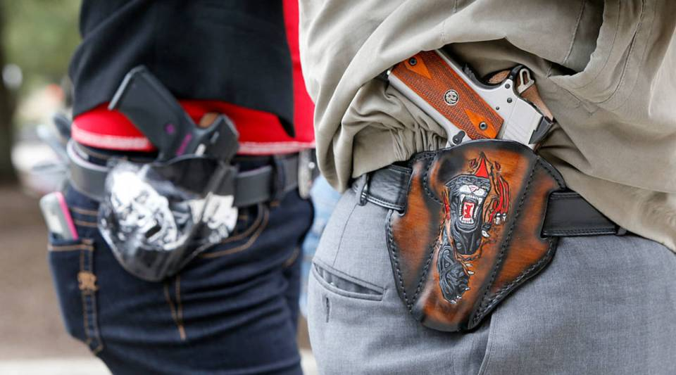 Art and Diana Ramirez of Austin with their pistols in custom-made holsters during and open carry rally at the Texas State Capitol on January 1, 2016 in Austin, Texas. On January 1, 2016, the open carry law took effect in Texas, and 2nd Amendment activists held an open carry rally.