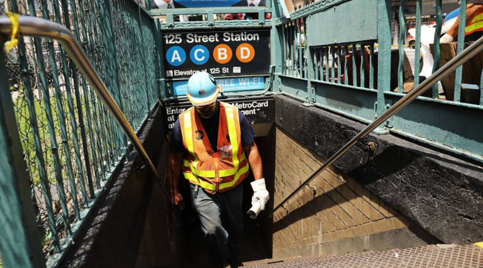 A Metropolitan Transportation Authority worker in New York City exits a Harlem subway station where a morning train derailed on June 27.