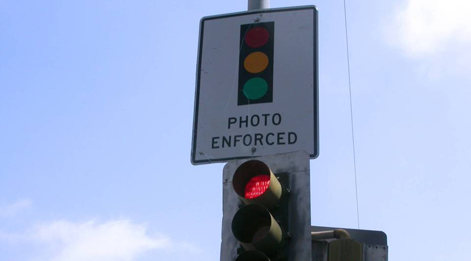 A red light camera warning for motorists in Los Angeles. The state is considering a proposal to reduce the cost of a  traffic ticket for low-income residents.