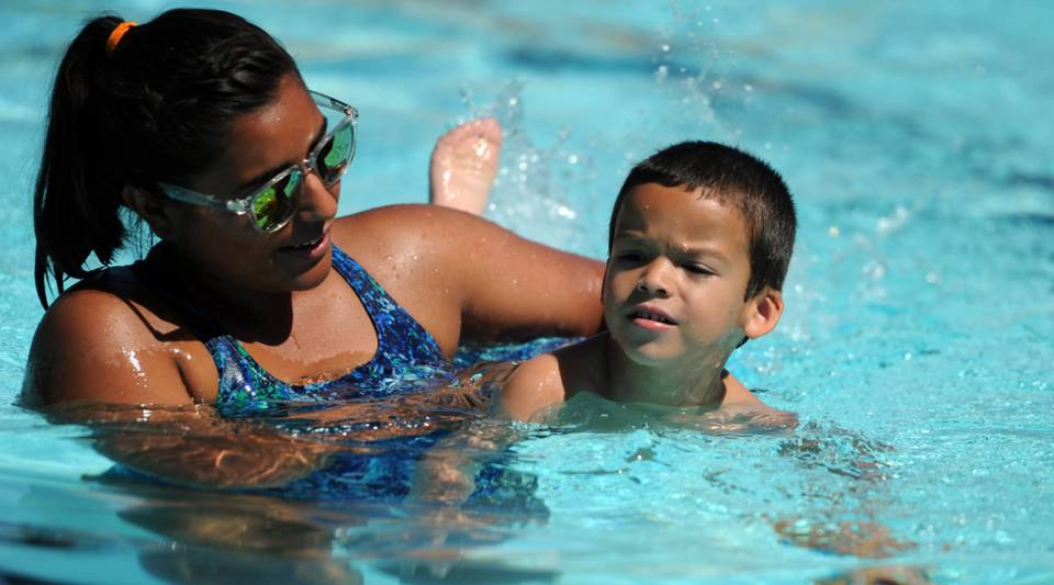 Swim instructor Jessica Raya assists Derek Muniz, 4, as he works on using his hands and feet at the same time during a class Monday at Thomas Pool in Fort Hood, TX.