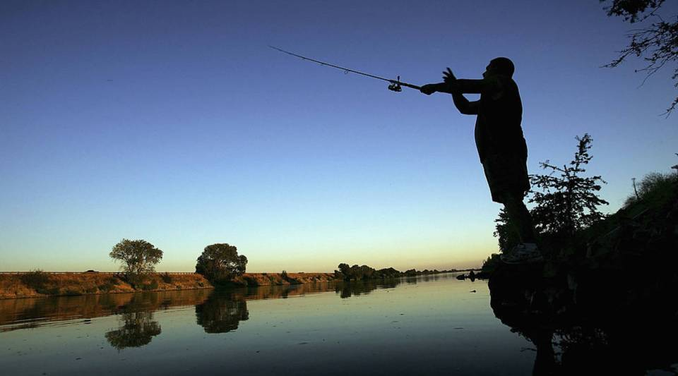 A fisherman casts his line into the Sacramento River.