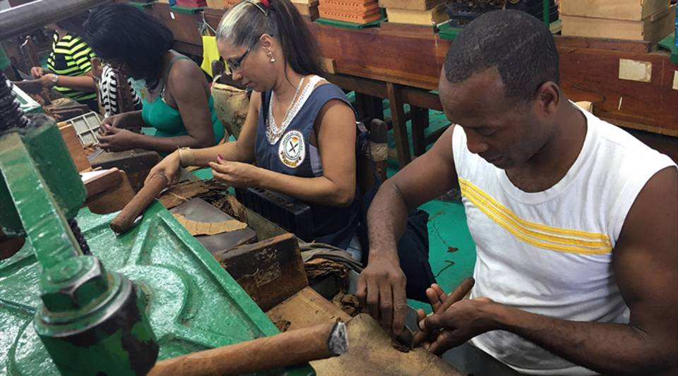 Workers at a Havana factory meticulously roll tobacco leaves into cigars. Supervisors measure and weigh each cigar to make sure it meets the high standards Cuban cigars are known for.