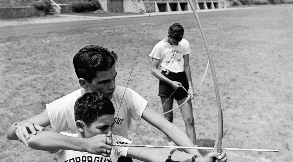 At the Admiral Farragut Academy summer camp a senior cadet instructs a younger camper on how to use a bow, circa 1950.