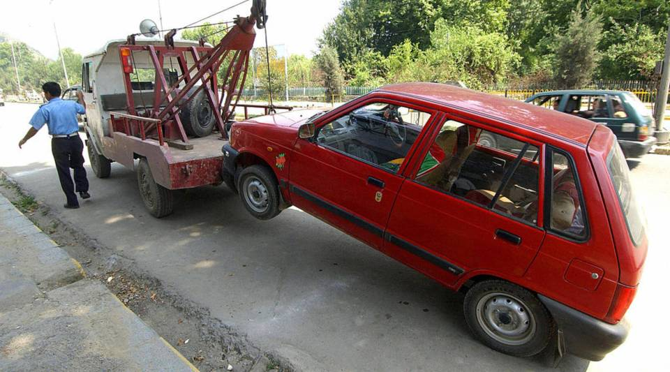 A tow-truck pulls a vehicle away from a non-parking zone.
