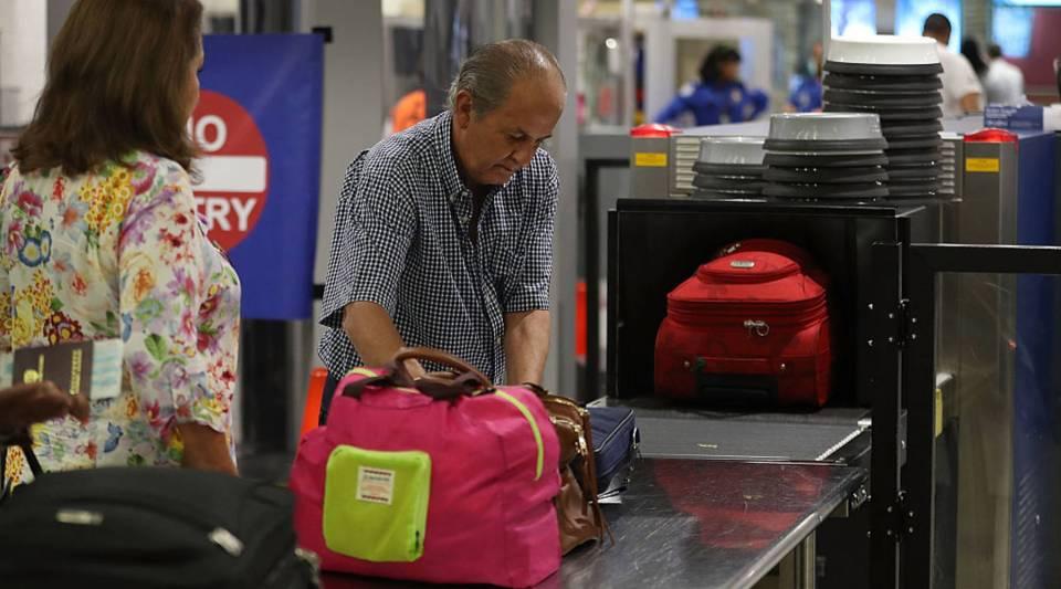 Travelers go through the TSA PreCheck security point at Miami International Airport in Miami, Florida.