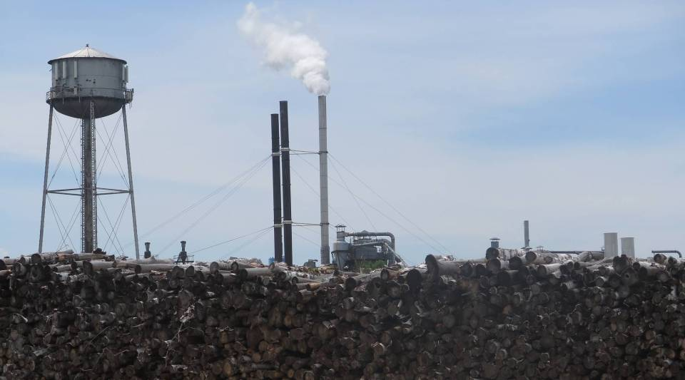 Smokestacks at the Diamond match factory in Cloquet tower over a pile of wood.