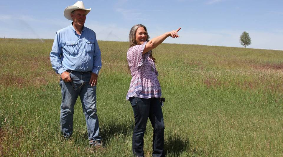 Farmer Christina Carpenter gestures toward one of the fields that will host campers during August's total solar eclipse. She and Grant Putnam (left) are taking advantage of the rare opportunity to host an eclipse festival on their farm, Organic Earthly Delights.