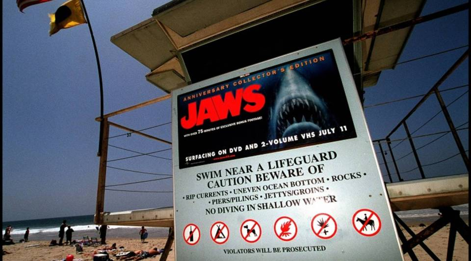 """A poster advertising the anniversary collector's edition of the movie """"Jaws"""" is posted on a lifeguard tower on Zuma Beach in Malibu, California, in 2000."""