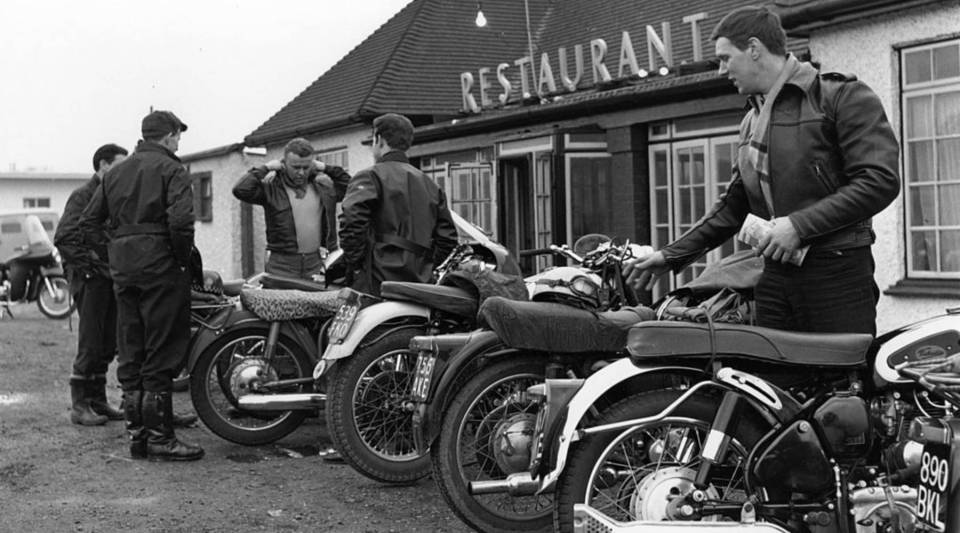 Motorcycle enthusiasts find a space for their prized possessions outside a cafe in 1960.
