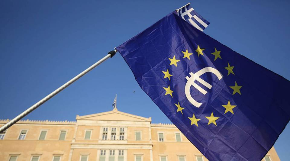 A European Union flag with the euro currency symbol waves in front to of the Greek Parliament in Athens, Greece.
