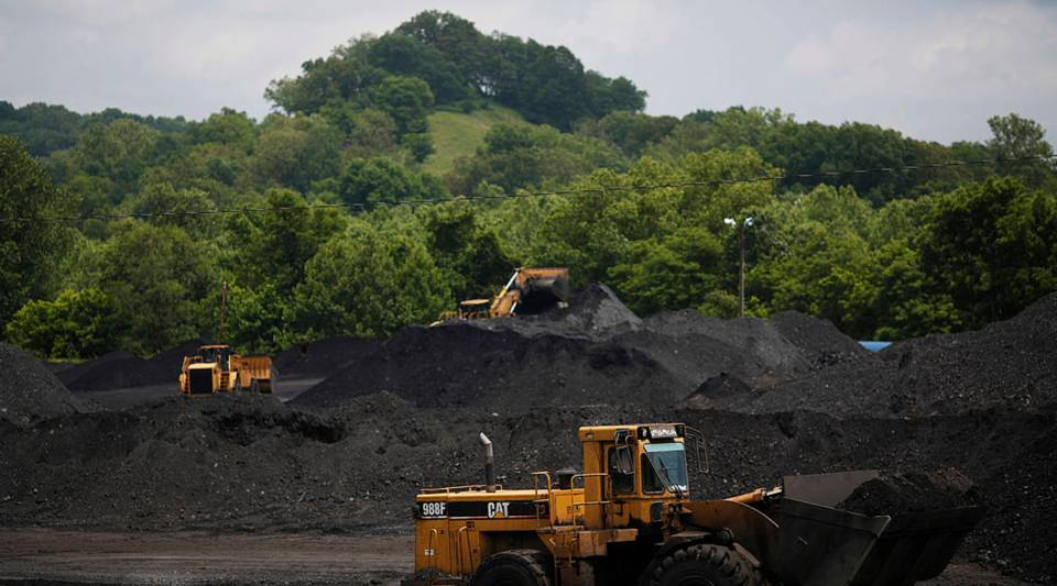 Caterpillar front-loading machinery operates on mounds of coal.