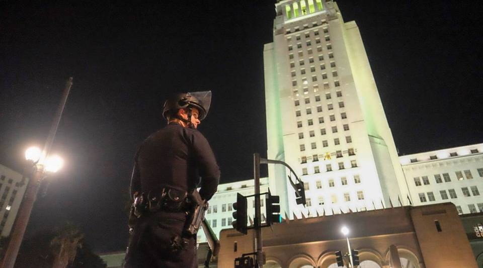 A police officer in riot gear stands guard outside City Hall during a protest in Los Angeles, California on November 2016.