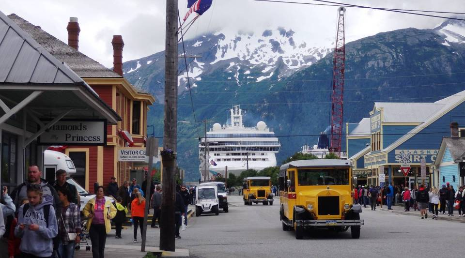 Tourists fill Skagway's Broadway Street on a busy July afternoon. A cruise ship looms in the background.