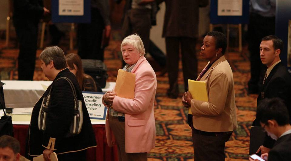 Job seekers wait in line to meet with a recruiter.
