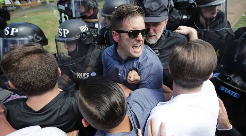 "White nationalist Richard Spencer (center) and his supporters clash with Virginia State Police in Emancipation Park after the ""Unite the Right"" rally was declared an unlawful gathering in Charlottesville, Virginia."