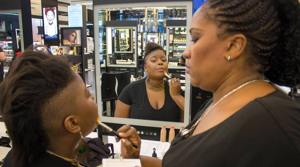 Bamike Ogunrinu, left, sits as New York City-based makeup artist Etzel Ecleston does her makeup with Fenty Beauty products. The brand, launched this month by popstar Rihanna, has been selling out online and in stores.