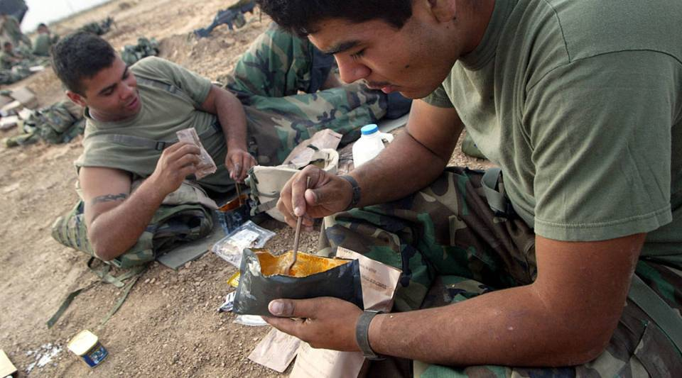 Marine Lance Corporal Pedro Rodriquez (L) from Methuen, Massachusetts and Lance Corporal Miguel Ochoa from Mountain View, California, of Task Force Tarawa, eat their meals, ready to eat during a maintenance stand down day April 10, 2003 near Kumayt, Iraq.