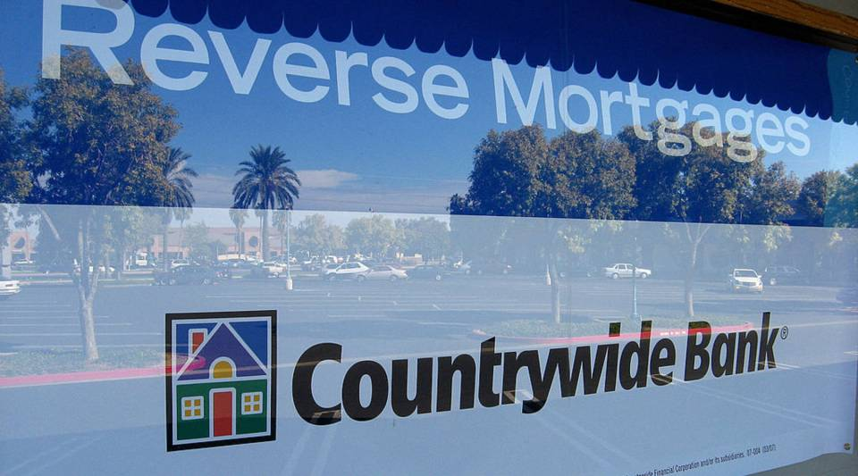 The reflection of blue skies and palm trees are seen in the window of a Countrywide banking and home loans location offering reverse mortgages in Sun City, Arizona.