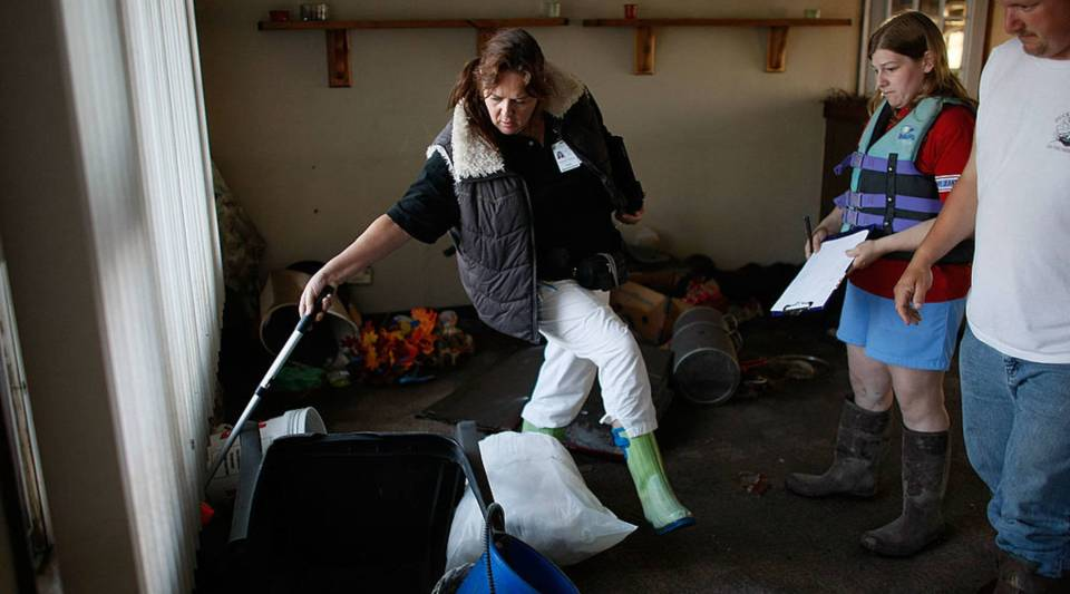 Jack Wheeler and his wife, Tami Wheeler, watch as a FEMA housing inspector measures their flooded home in 2008 in Oakville, Iowa.