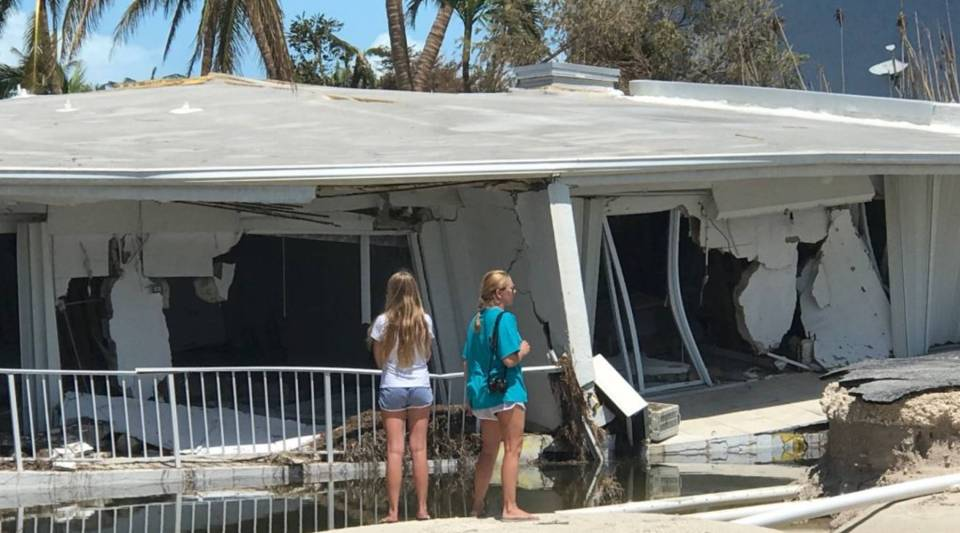 Two women look over severe damage to a residence following powerful Hurricane Irma on September 12, 2017 in Isamorada, a village encompassing six of the Florida Keys.