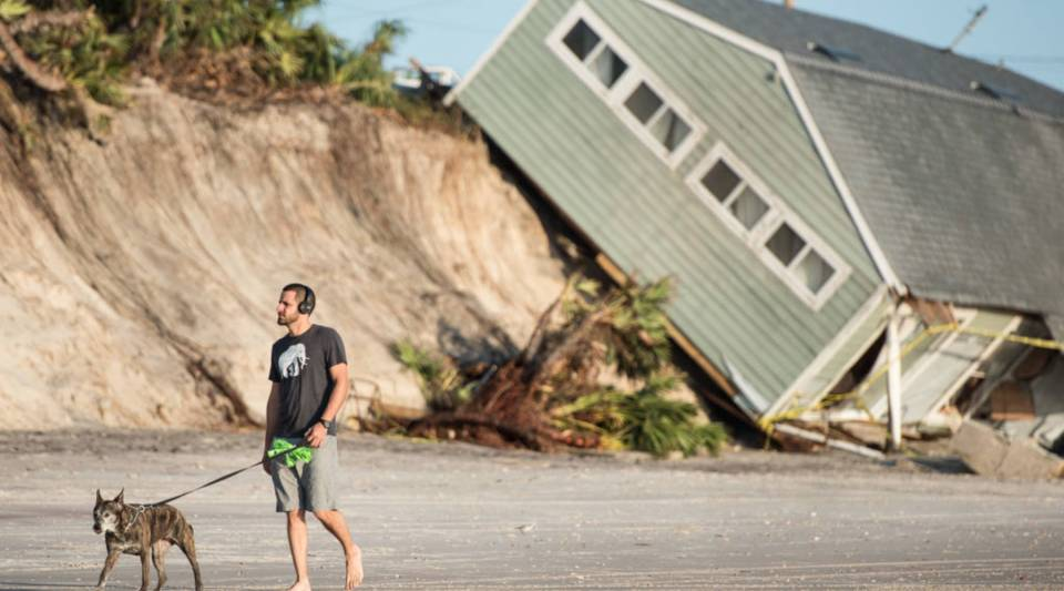 Jose Orosz walks his dog Karen by a beachfront home destroyed by Hurricane Irma on September 13, 2017 in Vilano Beach, Florida. Nearly 4 million people remained without power more than two days after Irma swept through the state.