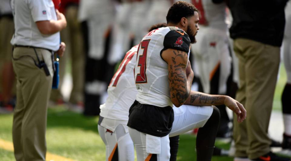 Tampa Bay Buccaneers Wide Receivers Mike Evans #13, and DeSean Jackson #11, take a knee during the national anthem before the game against the Minnesota Vikings on September 24, 2017 at U.S. Bank Stadium in Minneapolis, Minnesota.