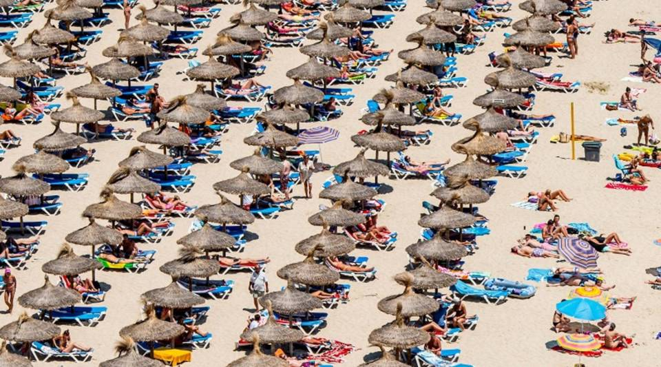 Fewer than half of U.S. workers use their vacation days, a U.S. Travel Association survey says. Above, tourists sunbathe on the Magaluf beach in Mallorca.