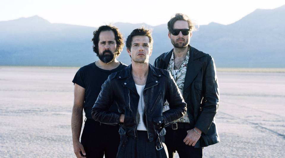 Brandon Flowers (center) and Ronnie Vannucci Jr. (left) from the band The Killers take our money inspired personality questionnaire.